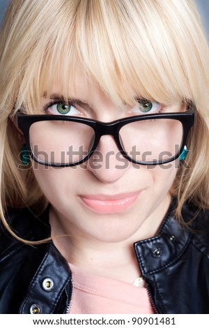 Portrait of young woman with blonde hair and green  eyes in glasses - stock photo