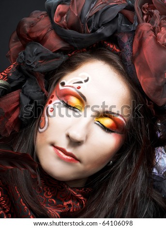 Portrait of young woman with creative make-up in black and red colors