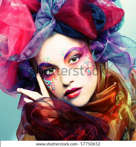 Portrait of young woman with creative make-up in doll style - stock photo
