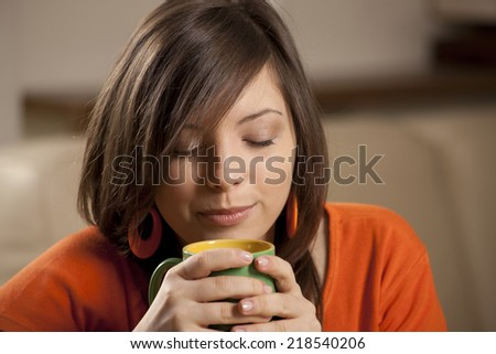 Portrait of young woman with cup of coffee or tea - stock photo
