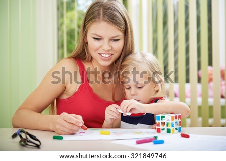 Portrait of young woman with cute preschooler child coloring at home. Concept of family leisure activity.