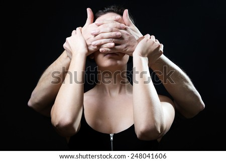 Portrait of young woman with eyes covered by a male hands. Concept of submission. - stock photo