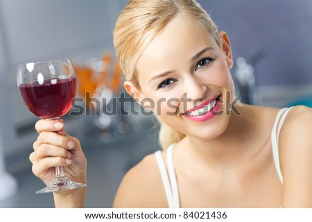 Portrait of young woman with glass of red wine, at home