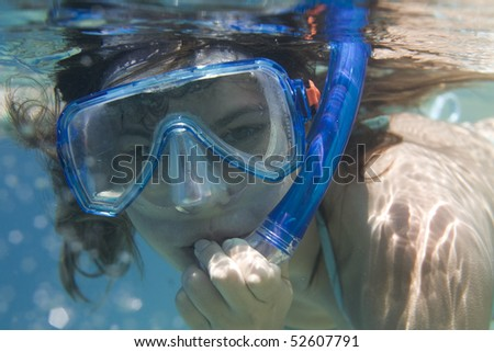 Portrait of young woman with goggles touching snorkel in red sea - stock photo