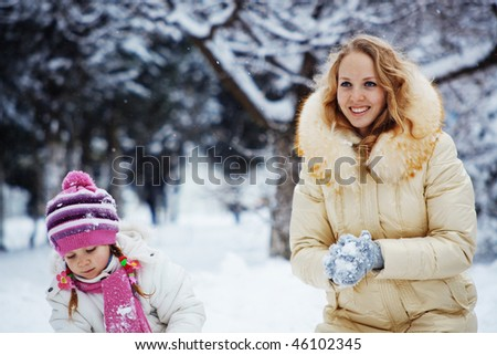 Portrait of young woman with kid girl playing snowballs in winter - stock photo