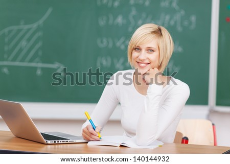 Portrait of young woman with laptop writing notes at desk in classroom - stock photo