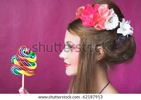 Portrait of young woman with lollipop and with pink flowers in her hair - stock photo