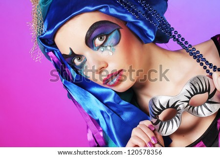 Portrait of young woman with mask  in creative theatrical image. - stock photo