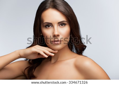 portrait of young woman with naked shoulders, on bright grey background - stock photo