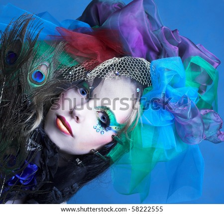 Portrait of young woman with peacock feathers - stock photo