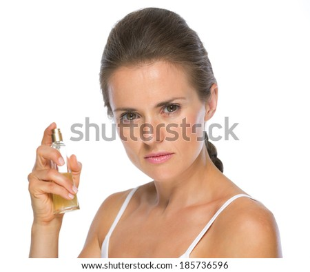 Portrait of young woman with perfume bottle - stock photo