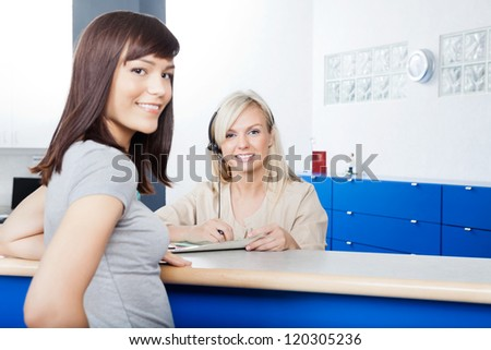 Portrait of young woman with receptionist filling form at desk in dentist's office - stock photo