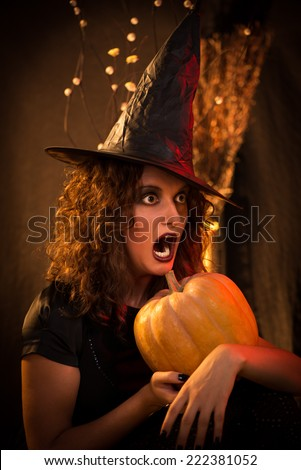 Portrait of young woman with scared face dressed like a witch. She wears dark clothing and holding a pumpkin in hands.