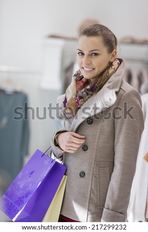 Portrait of young woman with shopping bags in store - stock photo