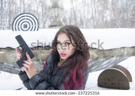 Portrait of young woman with snowflake in red brunette curly hair Cute girl with black pistol gun against  snowdrift cold winter trees in city park on old retro vintage fountain in forest background - stock photo