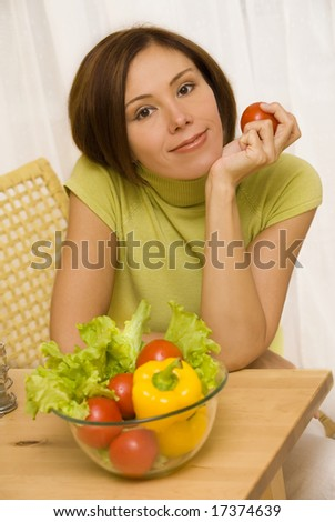 Portrait of young woman with tomato in her hand - stock photo