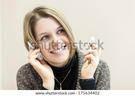 Portrait of young woman with two cellphones in hands - stock photo