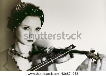 Portrait of young woman with violin on light background - stock photo