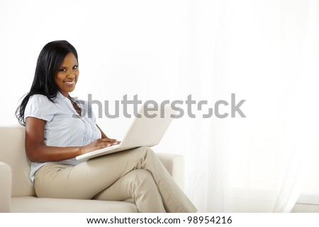 Portrait of young woman working on laptop while smiling to you - stock photo