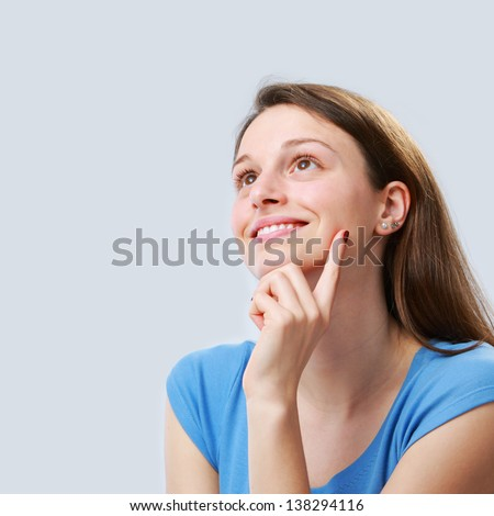 Portrait of young woman young woman looking up - stock photo