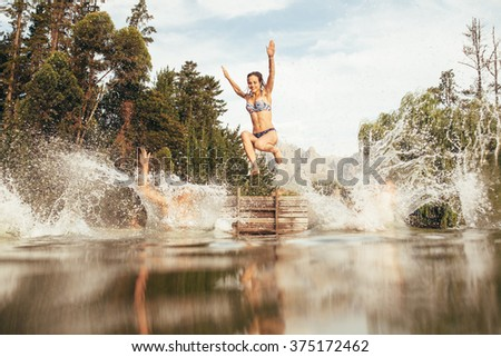 Portrait of young women jumping into a wilderness lake from the jetty. Young girl jumping from a pier at the lake - stock photo
