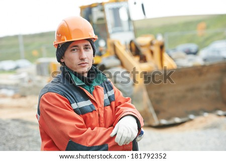 Portrait of young worker builder at construction site - stock photo