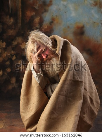 Portrait old beggar with a beard and mustache, wrapped in burlap, with pain and despair in his eyes, the studio on a brown-blue background - stock photo