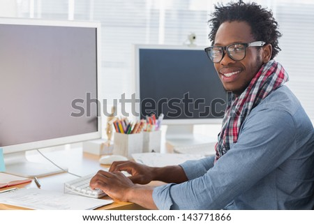 Portrait on a creative business worker on computer in a modern office - stock photo
