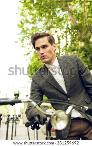 Portrait on a young handsome businessman leaning on his bicycle  - stock photo