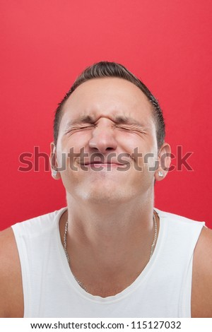 Portrait on a young man in white shirt on red background - stock photo