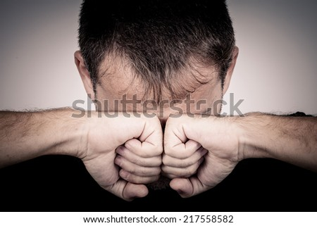 portrait one sad man standing near a wall and covers his face - stock photo