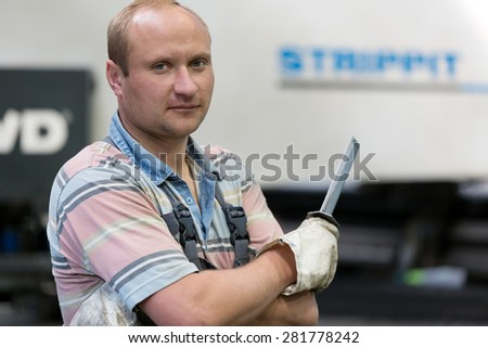 Portrait operator man worker at factory equipment background with deburring tool in hand for removing steel burrs from metal sheet or workpiece after a modification process  - stock photo