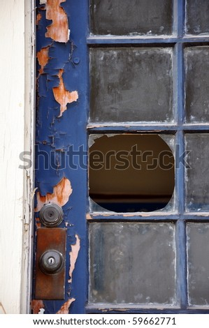 Portrait orientation close up of broken window pane in an old door with peeling paint. - stock photo