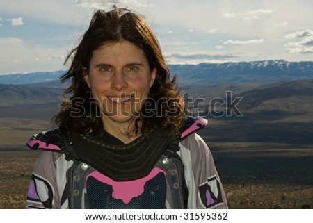 Portrait outdoors of a white female motocross rider all geared up - stock photo