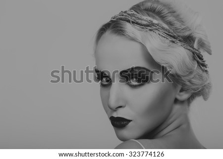 Portrait photo model on a dark background. Stylish makeup and jewelry. Model posing for the camera shows jewelry. Photo for fashion magazines and posters.