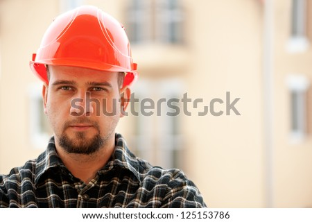 Portrait photo of a friendly and helpful construction worker - stock photo