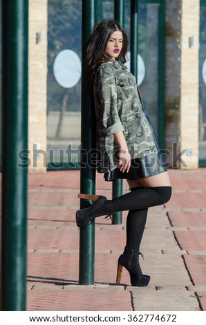 Portrait photo of a lady with bold purple big fleshy lips wear army jacket, long shocks, leather skirt and heels, full body length photo - stock photo