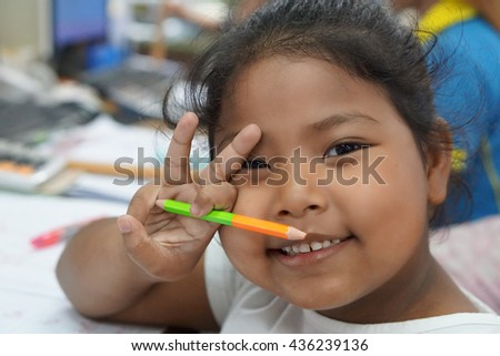 portrait photo of smiling innocent Thai girl while she holding color pencil in her hand and another hand  do V sign - stock photo