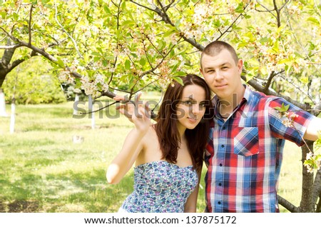 Portrait photograph of a beautiful young couple embracing outdoors while on picnic. - stock photo