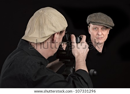 Portrait Photographer with camera on black - stock photo