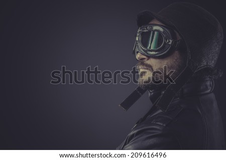 portrait pilot dressed in vintage style leather cap and goggles - stock photo