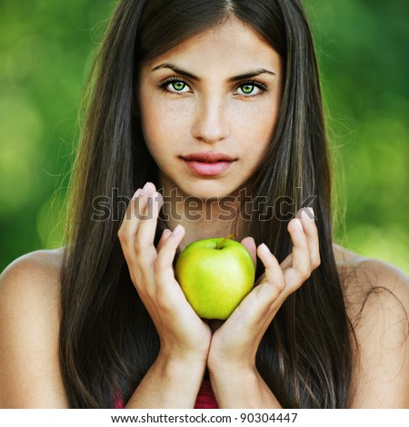 portrait pretty serious long-haired woman hands yellow apple background summer park - stock photo