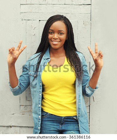 Portrait pretty smiling african woman having fun in city - stock photo