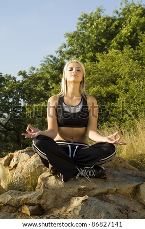 Portrait pretty woman meditating on rock lotus hands with gold light reflector - stock photo