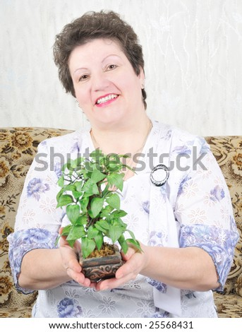 portrait pretty woman; woman hold in hand plant - stock photo