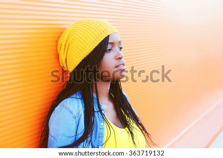Portrait pretty young african woman over orange background, profile view - stock photo