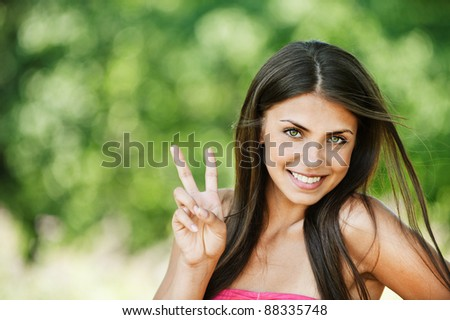 portrait pretty young brunette smiling shows victory sign background summer green park - stock photo