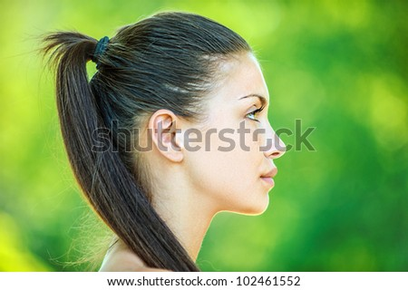 Portrait profile of face young beautiful woman, on green background summer nature. - stock photo