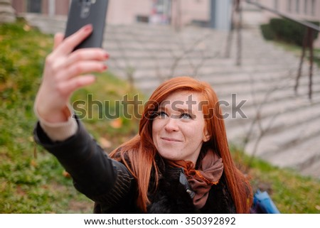 Portrait red head girl with mobile phone