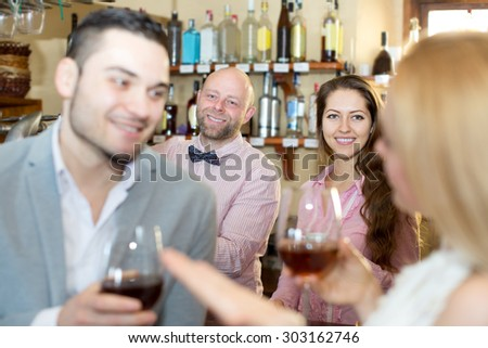 Portrait restaurant adult visitors waiting for table and drinking wine at tavern. Focus on the barman - stock photo
